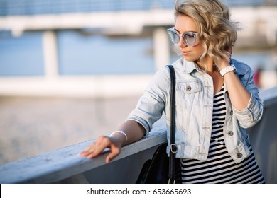 portrait of a young woman, blonde, glasses, outdoors in the park