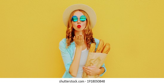 Portrait of young woman blowing her lips sending air kiss holding grocery shopping paper bag with long white bread baguette on a yellow background