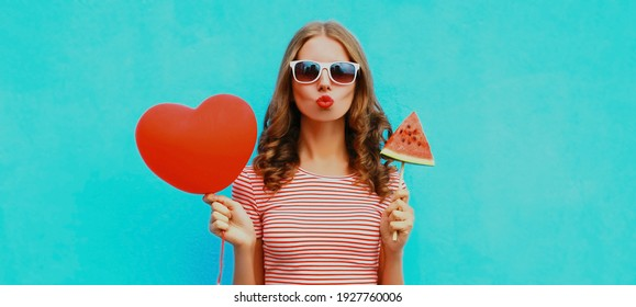 Portrait of young woman blowing her red lips with red heart shaped balloon and ice cream shaped slice of watermelon on a blue background