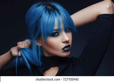 Portrait of a young woman with a blue color hair