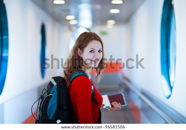 Portrait of a young woman in the boarding bridge, boarding an aircraft (color toned image)