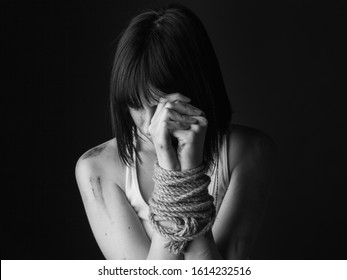 Portrait of  young woman with bound hands on black background. Black and white