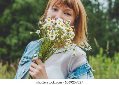 Portrait of young woman with a bouquet of chamomiles. Trees background.