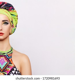 Portrait of a young woman with bright makeup and a fashionable headscarf. Light background. Beauty, fashion, makeup concept.