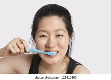 Portrait of a young woman brushing her teeth over light gray background