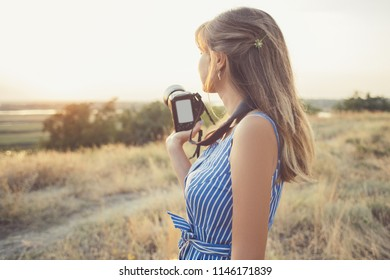 portrait of a young woman with a camera, nature photographer in the field, concept women's professions