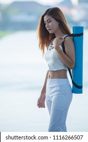 Portrait of young woman carrying yoga mat get ready for exercise on isolated background.