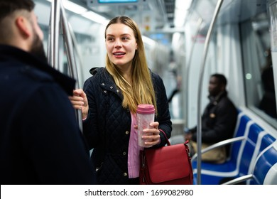 Portrait of young woman chatting friendly with her fellow traveler in modern subway car