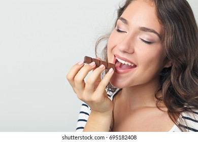 Portrait of young woman with chocolate on grey background