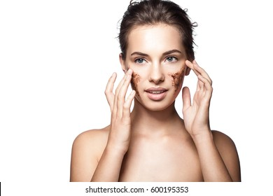 Portrait of a young woman with a coffee scrub on her face doing peeling skin isolated on white background