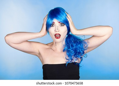 Portrait of young woman in comic  pop art make-up style.  Shoked female in blue wig on blue background.