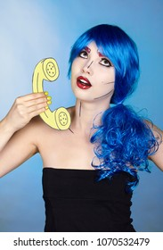 Portrait of young woman in comic  pop art make-up style.  Female in blue wig on blue background calls by phone.