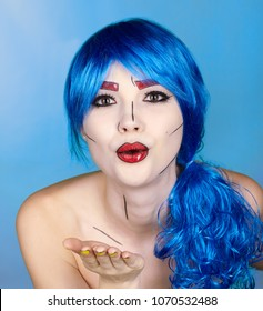 Portrait of young woman in comic  pop art make-up style.  Female in blue wig on blue background. The girl sends an air kiss