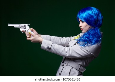Portrait of young woman in comic  pop art make-up style.  Female with gun in hand.