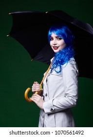 Portrait of young woman in comic  pop art make-up style. Female with umbrella on dark background.