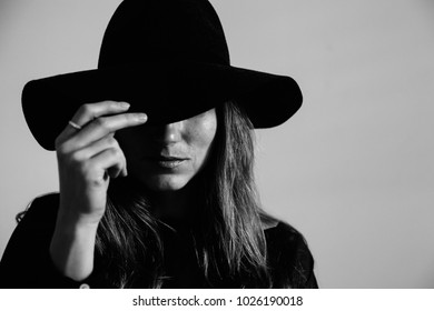 Portrait of a young woman in contrast black and white with face partially covered by a hat