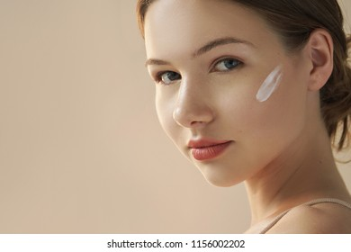 portrait of young woman with cosmetic cream on her face on beige background