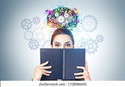 Portrait of young woman covering her face with black book standing near gray wall with colorful brain sketch with gears drawn on it. Concept of education and brainstorming