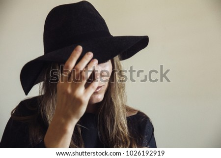 461e84c4b36 A portrait of a young woman covering her face partially with a fedora black  hat