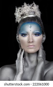 Portrait of a young woman with creative fantasy make up and body painting as Snow Queen or Ice Fairy