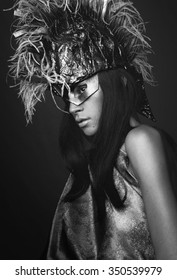 Portrait of young woman in creative head wear with feathers on dark background