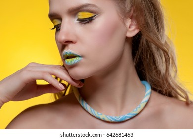 Portrait of a young woman with a creative make-up and decoration made of beads on a yellow background, looking away.