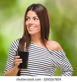 Portrait Of A Young Woman With Cup against a nature background