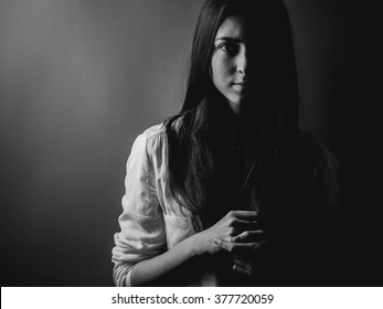 Portrait of young woman in darkness. High contrast , Black and white.