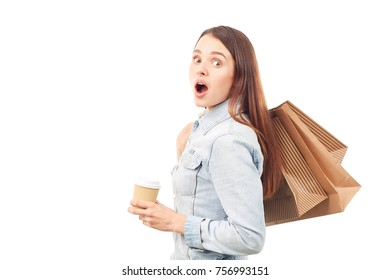 Portrait of young woman in denim jacket holding shopping bags and disposable coffee cup on white background