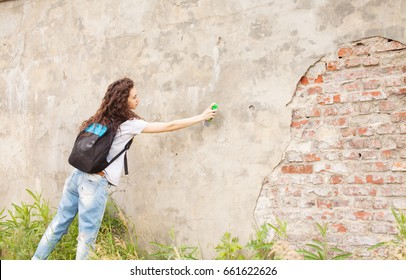 Portrait of young woman drawing graffiti with spray paint on street wall. Outdoors. Urban concept.