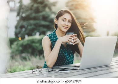 Portrait of young woman drinking coffee and using laptop at a cafe, Blogger woman reading new comments from followers