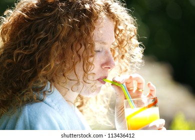 Portrait of a young woman drinking juice  outdoors