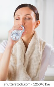 Portrait of young woman drinking water at gym after doing exercises