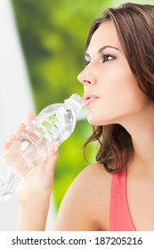 Portrait of young woman drinking water from bottle, outdoors. Focus on bottle.