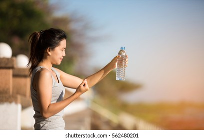 portrait of young woman drinking water after sporting
