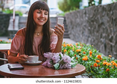 Portrait of young woman drinks cappuccino in a street cafe and speaks by phone. Blurred cityscape background.