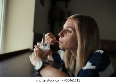Portrait of young woman drinks coffee latte in cafe