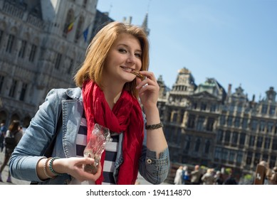 Portrait of a young woman eating chocolate on Grand place in Brussels