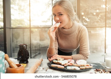 Portrait of young woman eating cookie heart. Beautiful young confectioner tasting fresh holiday treat, looking at camera. Homemade bakery, sweet pastry, winter holiday, love concept