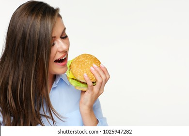 Portrait of young woman eating fast food burger. Isolated white back.