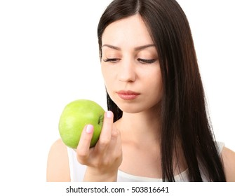 Portrait of young woman eating green apple isolated on white