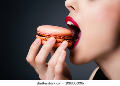 Portrait of a young woman eating a macaroon