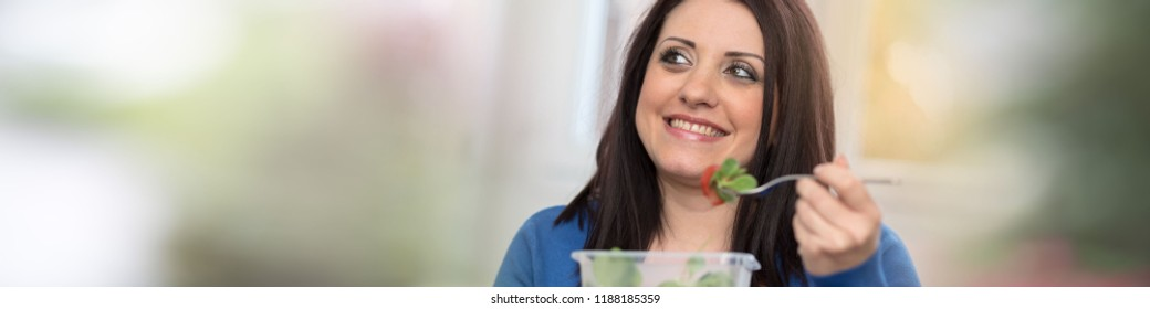 Portrait of young woman eating salad during break