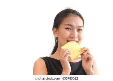 Portrait of young woman eating slice of bread