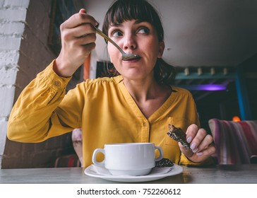 Portrait of young woman eating soup in a cafe