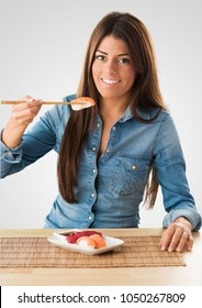Portrait Of A Young Woman Eating Sushi against a grey background