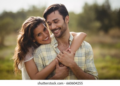 Portrait of young woman embracing man on sunny day at farm
