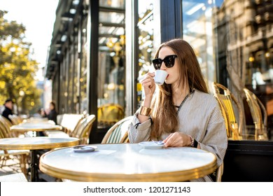 Portrait of a young woman enjoying coffee sitting outdoors at the traditional french cafe during the morning in Paris