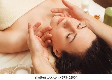 Portrait of young woman enjoying face massage. Closeup of beautiful woman relaxing under professional masseur hands. Body care, beauty, oriental spa, pleasure, resort concept