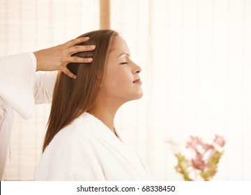 Portrait of young woman enjoying head massage with closed eyes, smiling.